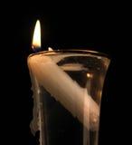 La vela ardiente fijó en un vidrio de líquido claro Foto de archivo