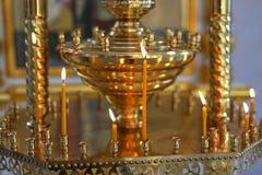 La vela de la iglesia quema en el altar delante del icono ortodoxo Fotografía de archivo