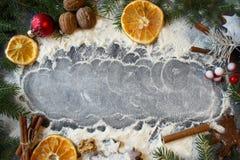 La vela de la Navidad en un fondo blanco adornado con las ramas del abeto, pan de jengibre, secó rebanadas y el canela anaranjado Fotografía de archivo