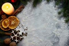 La vela de la Navidad en un fondo blanco adornado con las ramas del abeto, pan de jengibre, secó rebanadas y el canela anaranjado Foto de archivo libre de regalías