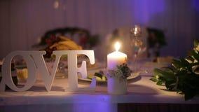 La vela del día de boda es una decoración hermosa en el restaurante almacen de video