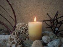 La vela que brilla intensamente, las piedras naturales del mar y secan las ramas, fondo abstracto Foto de archivo libre de regalías
