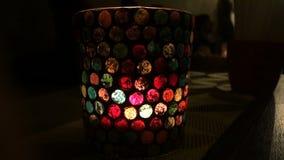 La vela quema en una palmatoria de cristal multicolora almacen de metraje de vídeo