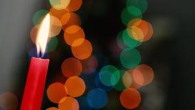 La vela roja en un fondo oscuro, vela de la Navidad en bokeh enciende el fondo, tarde de la Navidad, Año Nuevo, Navidad, coloread almacen de video