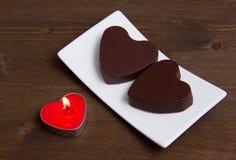 La vela y los chocolates en un corazón forman en la madera Imagen de archivo libre de regalías