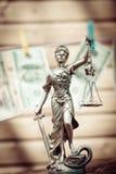 La venda de la escala de la tenencia de la justicia de la diosa o de la señora de Themis y los billetes de banco del dólar de USD fotos de archivo libres de regalías