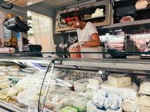 La vendeuse de femme au marché de ville vend des agriculteurs fromage et jambon Photos stock