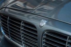 La vendita al dettaglio del logo sovrano del giaguaro sulla parte anteriore grigia dell'automobile ha parcheggiato nella via fotografia stock