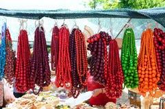 La vendita dei gioielli variopinti delle belle donne ha fatto delle perle di legno Fiera - una mostra degli artigiani pieghi fotografie stock