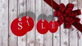 La vendita rossa etichetta l'attaccatura contro legno con l'arco festivo illustrazione di stock