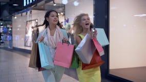 La vendita stagionale, donne del cliente affretta agli sconti in boutique al centro commerciale durante venerdì nero stock footage