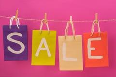 La vendita variopinta firma sui sacchetti della spesa che appendono sulla corda isolata sul rosa Fotografia Stock