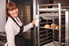 La venditora allegra sta lavorando nel forno con la gioia Fotografia Stock Libera da Diritti