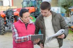 La venditora che mostra i trattori marca a caldo le capacità al cliente dell'agricoltore Fotografia Stock