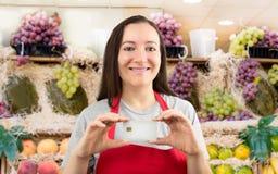 La venditora sta risparmiando con la carta di credito al negozio della frutta Fotografia Stock