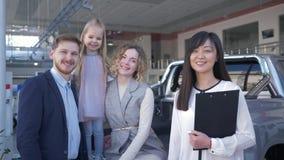 La venta acertada del coche, encargado feliz de la mujer sacude las manos con los compradores de la familia del automóvil en la s almacen de metraje de vídeo