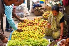 La venta asiática de la mujer da fruto en el mercado de la muchedumbre Fotos de archivo libres de regalías