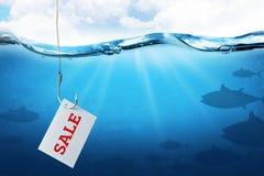 La venta de la inscripción en la hoja como cebo para los compradores Gancho de pesca con cebo de los pescados como símbolo del en fotografía de archivo libre de regalías