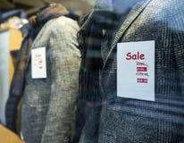La venta de la palabra en la ventana de la tienda de la tienda de ropa Fotos de archivo
