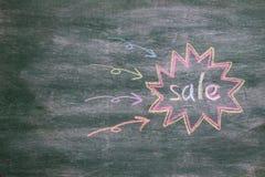 La venta escribe en la pizarra Imagen de archivo