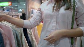 La venta estacional, muchacha sonriente feliz del comprador elige e intenta la nueva ropa delante del espejo en tienda durante de metrajes