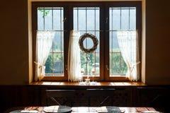 La ventana adorna por la guirnalda del beautifyl dentro de la cabaña Foto de archivo libre de regalías