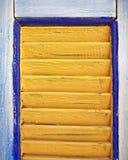 La ventana amarilla shutters el primer, fondo colorido Fotografía de archivo libre de regalías