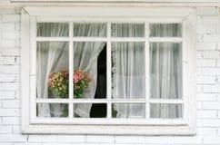 La ventana blanca horizontal con las cortinas, un ramo de flores en el windowsil Imagen de archivo libre de regalías