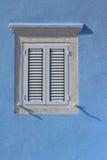 La ventana cerrada con los obturadores de madera blancos se cierra encima de vertical Foto de archivo libre de regalías