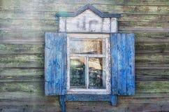 La ventana con el arquitrabe tallado de madera en la casa de madera vieja en la ciudad rusa vieja Fotografía de archivo