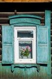 La ventana con el arquitrabe tallado de madera en la casa de madera vieja en la ciudad rusa vieja Fotos de archivo libres de regalías