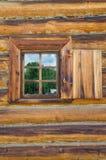 La ventana con el arquitrabe tallado de madera en la casa de madera vieja en la ciudad rusa vieja Imágenes de archivo libres de regalías