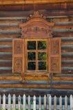 La ventana con el arquitrabe tallado de madera en la casa de madera vieja en la ciudad rusa vieja Imagenes de archivo