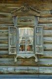 La ventana con el arquitrabe tallado de madera en la casa de madera vieja en la ciudad rusa vieja Fotografía de archivo libre de regalías