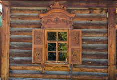 La ventana con el arquitrabe tallado de madera en la casa de madera vieja en la ciudad rusa vieja Imagen de archivo