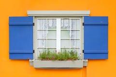 La ventana con la flor y los obturadores azules se abren en la pared amarilla Fotografía de archivo