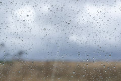 La ventana con lluvia cae sobre el vidrio fuera del paisaje natural fotos de archivo