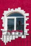 La ventana de la casa en un exterior coloreado Imagen de archivo