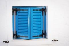 La ventana de madera azul shutters con los respiraderos en una pared de piedra blanca Fotografía de archivo libre de regalías