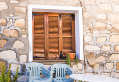 La ventana de madera marrón rústica shutters con el viejo fondo de la pared de piedra Foto de archivo