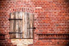La ventana de madera roja marrón cerrada con el metal aherrumbrado se articula en una pared de ladrillo roja sucia Foto de archivo libre de regalías