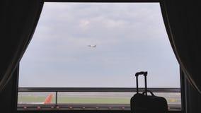 La ventana del hotel cerca del aeropuerto y del avión que sacan en el fondo de una maleta o de un equipaje metrajes