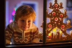 La ventana que hace una pausa sonriente del muchacho en el tiempo de la Navidad y el sostenerse pueden Imágenes de archivo libres de regalías