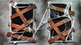 La ventana se cubre con madera y la telaraña en Halloween imagen de archivo