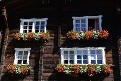 La ventana suiza del chalet del registro con el geranio rojo florece imagen de archivo
