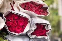 La vente fleurit - un bouquet des roses rouges/rose enveloppées en papier Images libres de droits