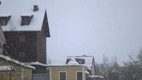 La ventisca cae en los tejados de la casa blancos y la nieve pura metrajes
