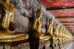 La veranda di dora le sculture di Buddha a Wat Suthat, Bangkok della Tailandia Fotografia Stock