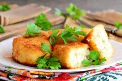La verdura agglutina con le uova su un piatto bianco Dolci casalinghi delle patate e del cavolfiore farciti con le uova affettate Fotografia Stock