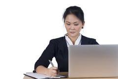 La verticale de la femme d'affaires avec l'ordinateur portable écrit sur un document à h Photos stock